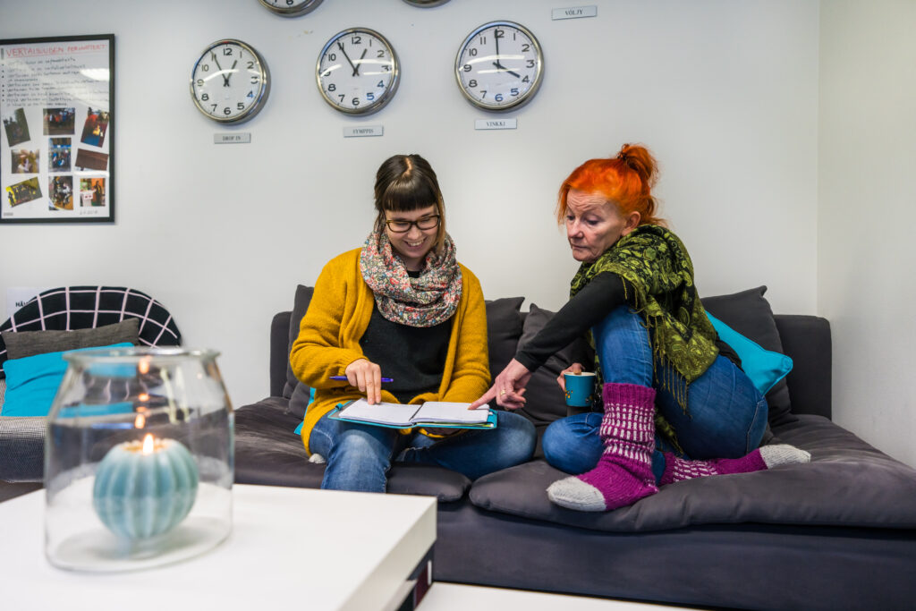 Kaksi naista istuu rennosti vierekkäin sohvalla ja katselee yhdessä toisen naisen sylissä olevaa muistivihkoa.