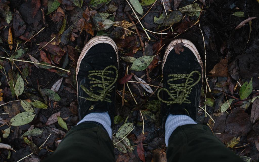 Jalat lehtien peittämällä syksyisellä maalla ylhäältäpäin kuvattuna.